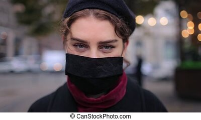 Portrait of young woman wearing medical mask while standing on street. Brunette in warm clothing outdoors