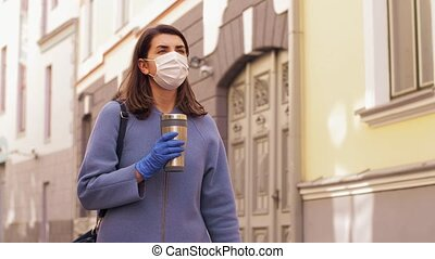 woman in medical mask with tumbler walking in city