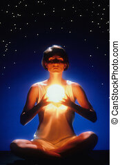 Front view of a woman meditating with crossed legs and eyes closed while holding a glowing ball. She is sitting in front of a starry night-time background. Vertical format.