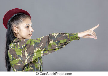 Woman in military clothes pointing to the right.