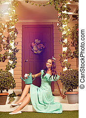 Woman in mint dress sitting on a porch