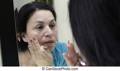 Woman in Mirror Looking at Her Skin Handheld - Handheld over...