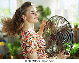woman in modern house in sunny hot summer day fanning herself