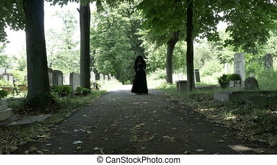 Woman in mourning black clothes walking slowly on alley in cemetery holding a flower crown in her hand portrait of sorrow and loneliness