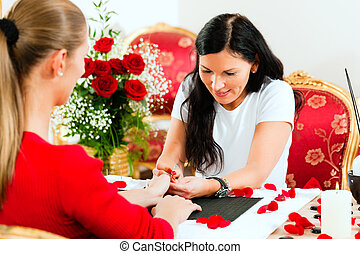 Woman in nail salon receiving manicure - Woman in a nail...