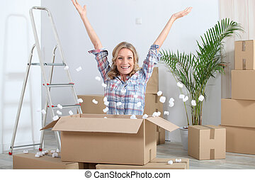 Woman in new home surrounded by boxes