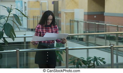 woman in office looks to drawing on large sheets of paper