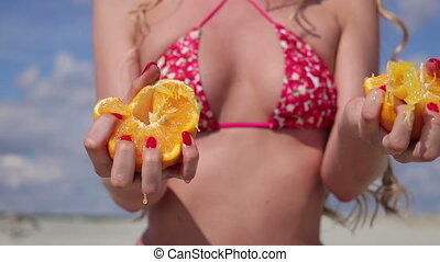 Woman in open swimsuit squeezing citrus by hands - Ripe...