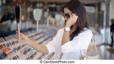 Woman In Optical Store Choosing Eyeglasses - Young woman...