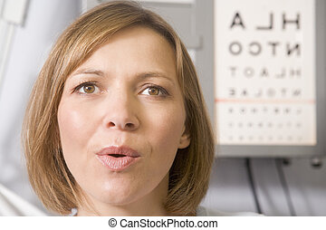 Woman in optometrist\'s exam room taking deep breath