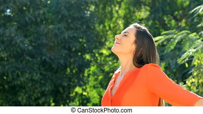 Woman in orange breathing fresh air in a park