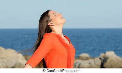 Woman in orange breathing fresh air on the beach - Woman in...
