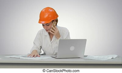Woman in orange hardhat calling the phone discussing constraction plan on white background.