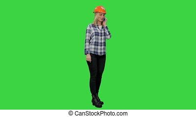 Woman in orange hardhat calling the phone on a Green Screen, Chroma Key.