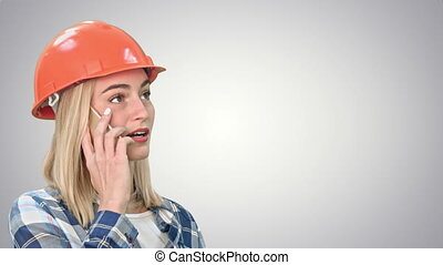Woman in orange helmet having a phone call discussing the problem with object on white background.