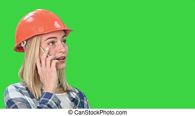 Woman in orange helmet having a phone call discussing the problem with object on a Green Screen, Chroma Key.
