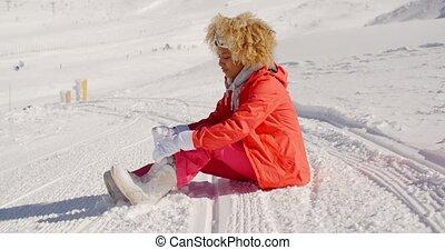 Woman in orange snowsuit sitting on ski slope - Single young...