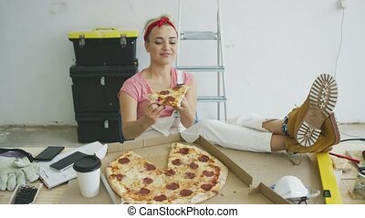 Woman in overalls eating pizza at workplace - Beautiful...