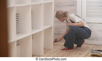 Woman in overalls sitting in a corner causes paint brush on the floor