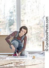 Woman in overalls working on floor in home