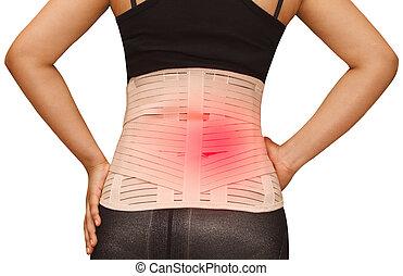 Woman in pain from back injury wearing lumbar brace corset