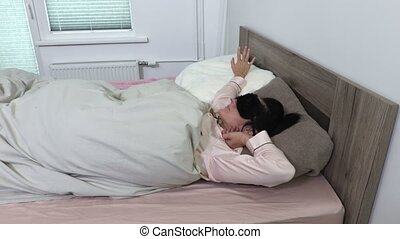 Woman in pajama and sleeping mask lazy waking up in the...