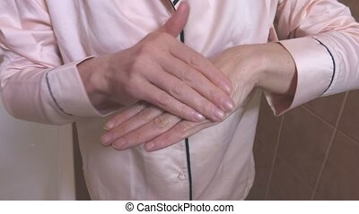 Woman in pajama applying cream on hands