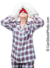 Woman in pajamas can not fall asleep, covered her head with a pillow, portrait on a white background