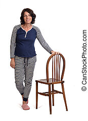 woman in pajamas playing with a chair on white background,