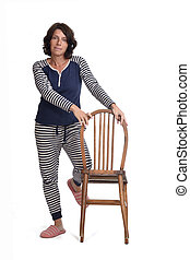 woman in pajamas playing with a chair on white background,  the knee above the chair