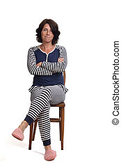 woman in pajamas sitting o a chair on white background, legs and arms crossed