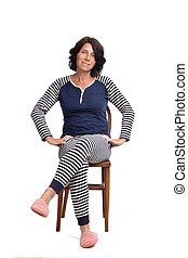 woman in pajamas sitting o a chair on white background, legs crossed and hands on hip
