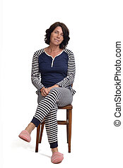 woman in pajamas sitting o a chair on white background, legs crossed