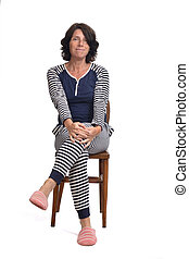 woman in pajamas sitting o a chair on white background