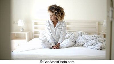 Woman In Pajamas Sitting On Bed - Young happy afro american...