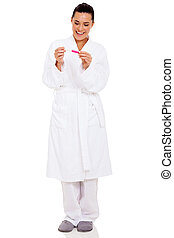 woman in pajamas with positive pregnancy test