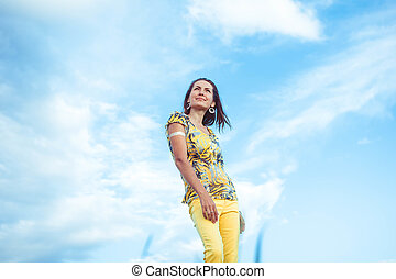 Woman in pants sky - Woman in yellow trousers stands against...