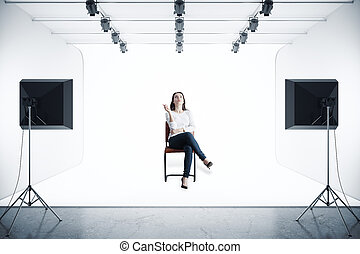 Woman in photo studio - Attractive woman sitting on chair in...