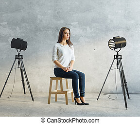 Woman in photo studio - Attractive young woman sitting in...