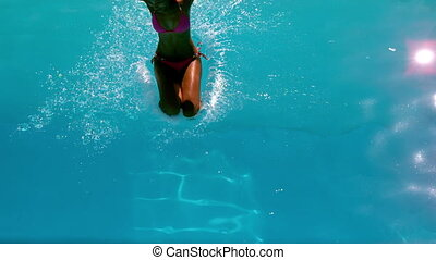 Woman in pink bikini jumping into pool