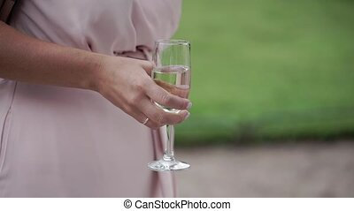 Woman in pink dress with glass of sparkling wine at the party