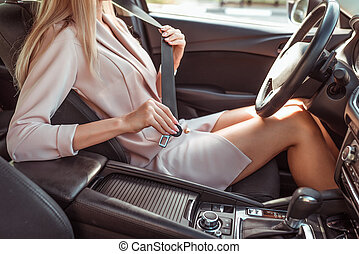 woman in pink jacket fastens her seat belt in summer in passenger compartment. Automatic gearbox, steering wheel and armrest. Tanned figure. Safety movement, activation of airbags.