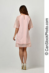 Woman in pink pastel color winter dress standing backwards rear view from behind