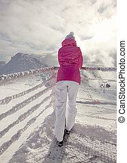 Woman in pink ski jacket leaning on snow covered rail, looking at ski piste, with sun and clouds backlight in background.