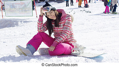 Woman in pink snowsuit with snowboard