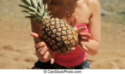 Woman in pink T-shirt in his hands rolls pineapple fruit on the beach.