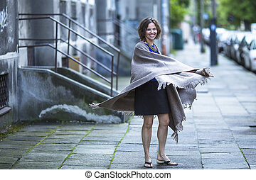 Woman in poncho at evening street.