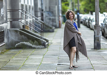 woman in poncho standing on street