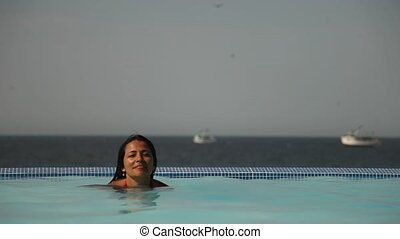 Woman in Pool in front of the Ocean
