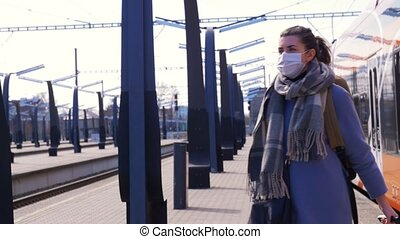 woman in protective face mask at railway station - health, ...